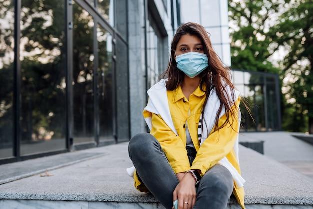 Ragazza che indossa la maschera in posa sulla strada. moda durante la quarantena dell'epidemia di coronavirus.