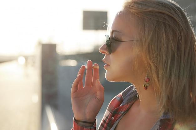 Ragazza che indossa occhiali da sole e fumo