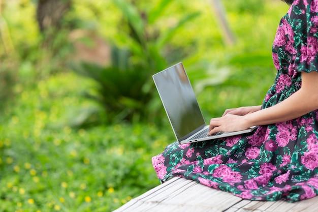 Ragazza che indossa un abito floreale seduto con il suo computer portatile