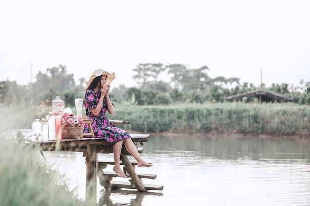 Ragazza che indossa un abito floreale seduto sul lungomare