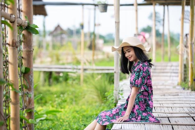 Ragazza che indossa un abito floreale tsitting su un pezzo di legno