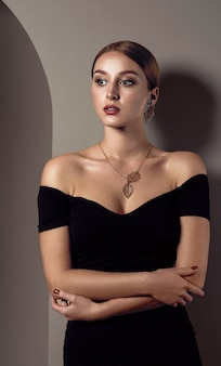 Ragazza che indossa un abito nero con spalle scoperte e foglie a forma di collana d'oro