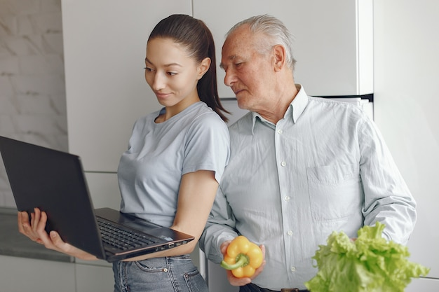 Ragazza che insegna a suo nonno come usare un computer portatile