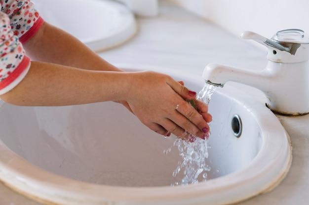 Ragazza che lava la mano nel lavandino