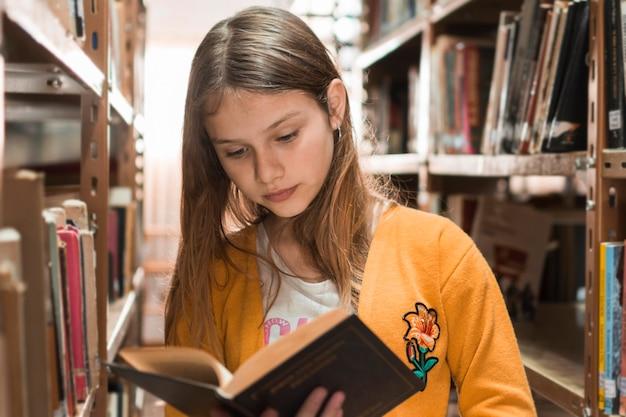 Ragazza che legge il libro tra librerie