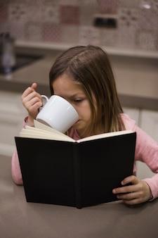Ragazza che legge libro e bere