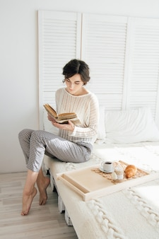 Ragazza che legge un libro a colazione