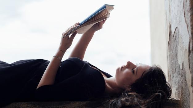 Ragazza che legge un libro a faccia in su