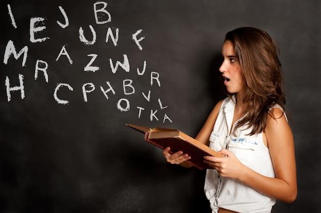 Ragazza che legge un libro con le lettere che volano via