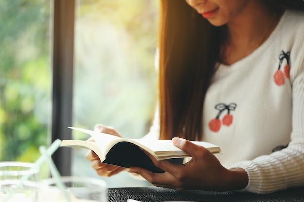 Ragazza che legge un libro dalla finestra di mattina.