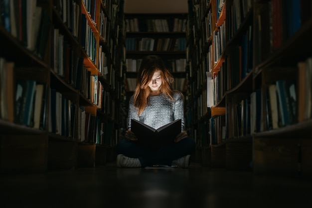 Ragazza che legge un libro in biblioteca, seduta sul pavimento. la ragazza in biblioteca