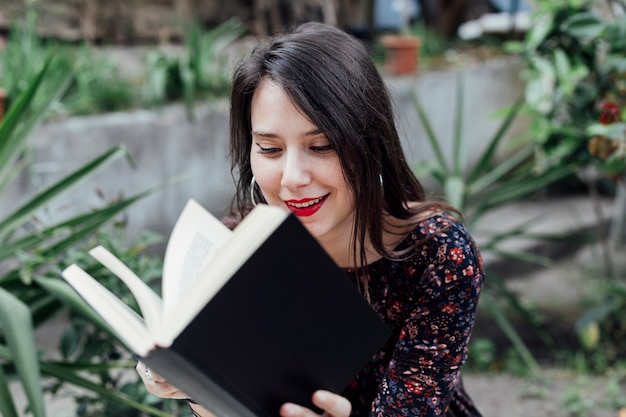 Ragazza che legge un libro in strada