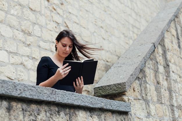 Ragazza che legge un libro in una giornata ventosa