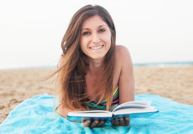 Ragazza che legge un libro sulla spiaggia