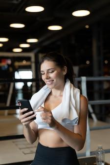 Ragazza che manda un sms mentre fa una pausa in una palestra. legge un messaggio