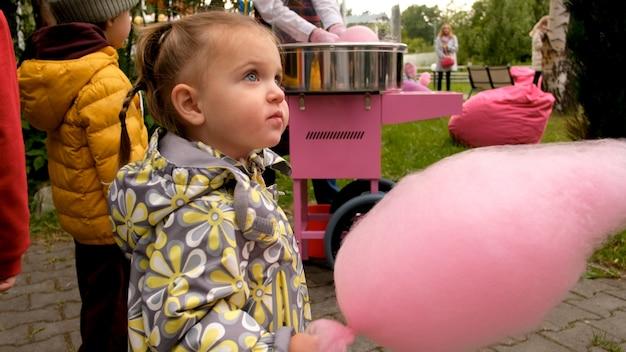 Ragazza che mangia il filo di zucchero candito nel parco