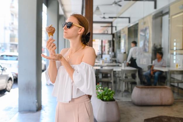 Ragazza che mangia il gelato che indossa gli occhiali da sole rotondi dello specchio