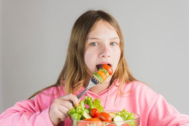 Ragazza che mangia insalata di verdure sana fresca in ciotola di vetro