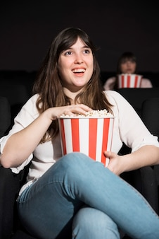 Ragazza che mangia popcorn nel cinema