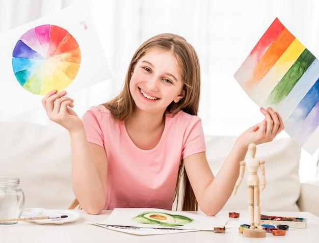 Ragazza che mostra la sua collezione di dipinti ad acquerello
