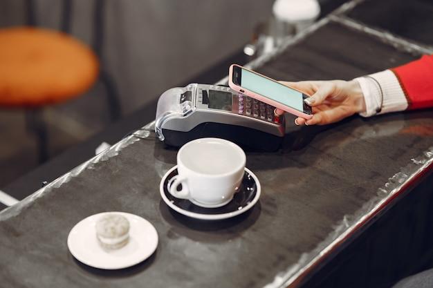 Ragazza che paga per il suo latte con uno smartphone con la tecnologia pay pass senza contatto