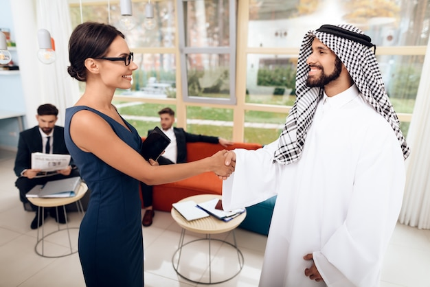 Ragazza che parla con uomini d'affari arabi in un business.