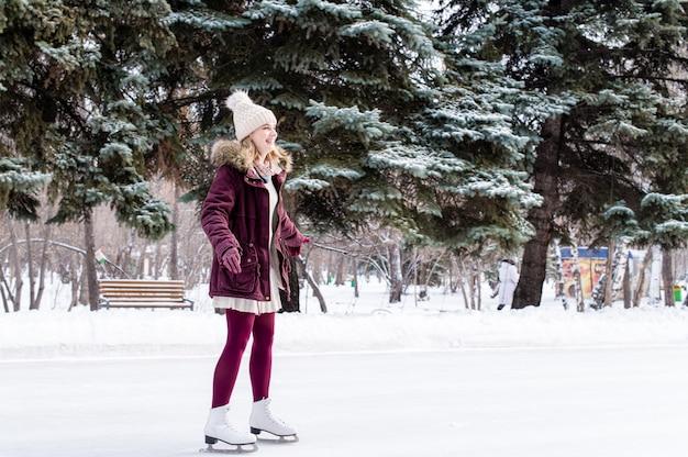 Ragazza che pattina sul lago congelato nel parco nevoso di inverno