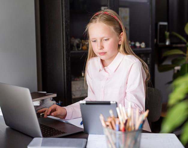 Ragazza che per mezzo del suo computer portatile e di un tablet per le lezioni online