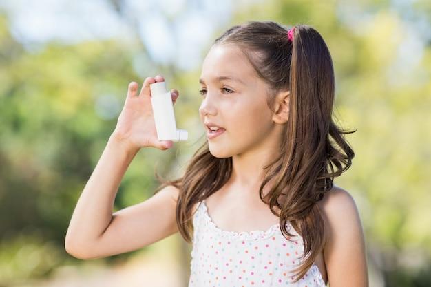 Ragazza che per mezzo di un inalatore per l'asma