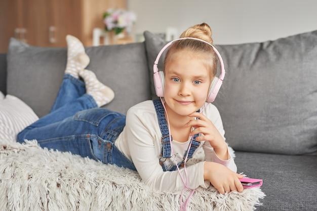 Ragazza che pone sul divano in cuffia, ascoltando la musica con il suo smarthphone