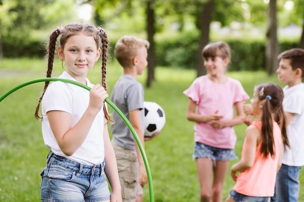 Ragazza che posa con il hula-hoop accanto agli amici