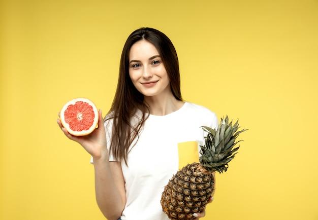 Ragazza che posa con la metà del pompelmo e un ananas