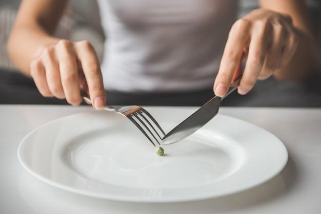 Ragazza che prova a mettere un pisello sulla forcella. concetto di dieta