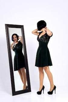 Ragazza che prova il vestito corto e si guarda allo specchio
