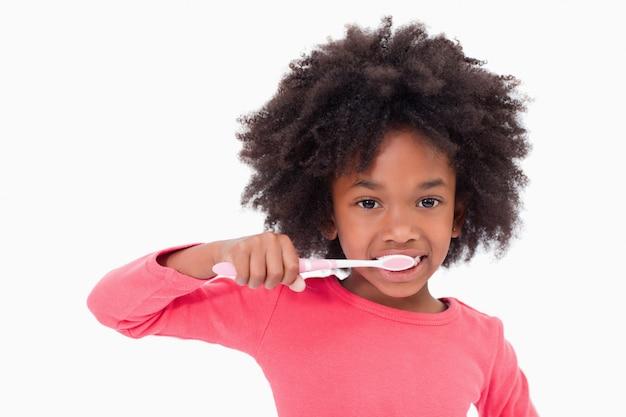 Ragazza che pulisce i suoi denti contro una priorità bassa bianca