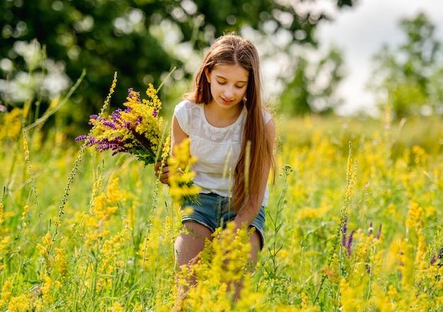 Ragazza che raccoglie i fiori sul campo