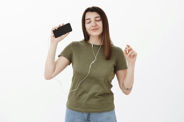 Ragazza che raggiunge il nirvana e le emozioni positive, ha vibrazioni positive dal suono fantastico degli auricolari, ascolta musica che balla sensualmente con gli occhi chiusi e un sorriso felice, alzando la mano con lo smartphone