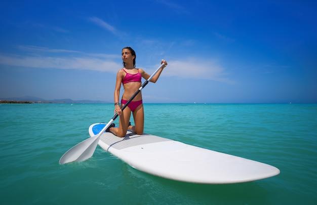 Ragazza che rema sulle ginocchia su paddle surf sup