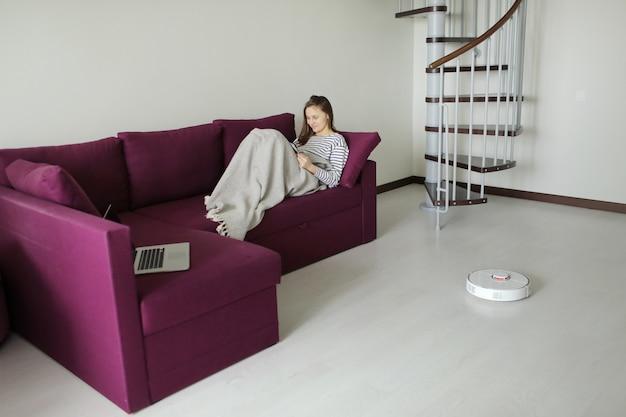 Ragazza che riposa a casa sul divano mentre l'aspirapolvere robot fa i lavori di casa