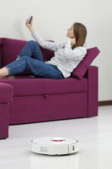 Ragazza che riposa a casa sul divano mentre l'aspirapolvere robot pulisce
