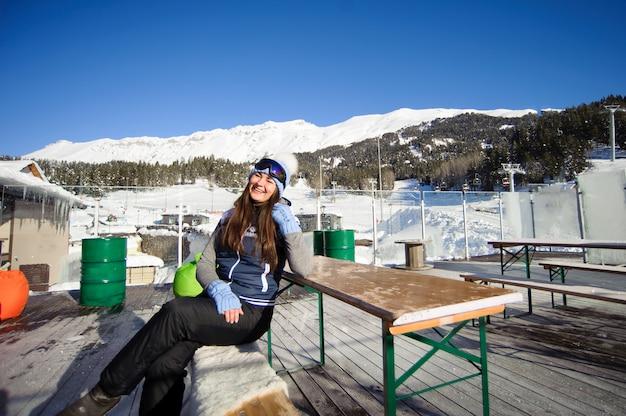 Ragazza che riposa dallo sci in una stazione sciistica di un caffè ai piedi delle montagne