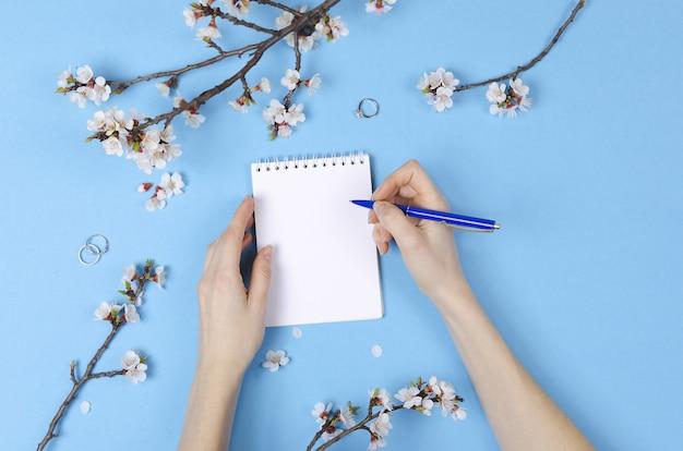 Ragazza che scrive la lista dei desideri per i piani futuri. composizione piatta con fiori, blocco note