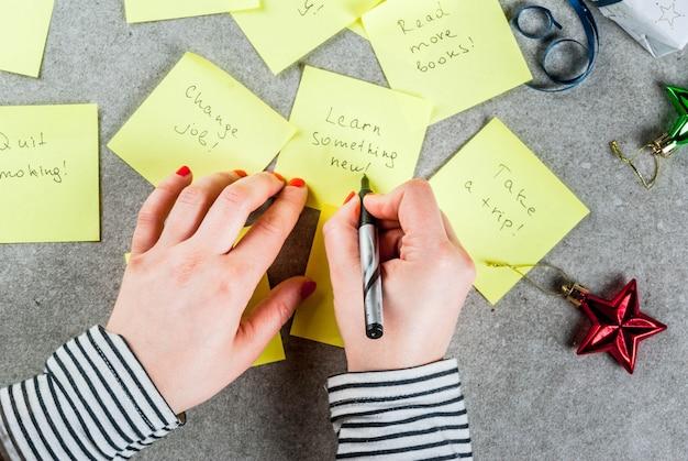 Ragazza che scrive risoluzioni di nuovi anni mani in foto tavolo in pietra grigia con note adesive colorate con risoluzioni e penna di capodanno popolari