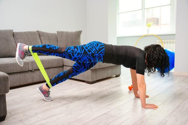 Ragazza che si allena a casa. donna di sport che si esercita con la fascia di resistenza.