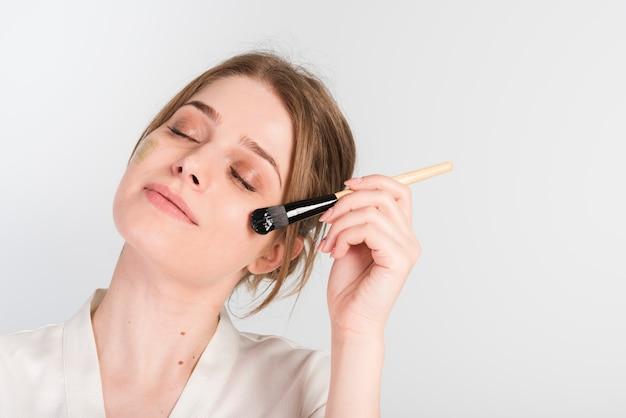 Ragazza che si applica prodotto cosmetico