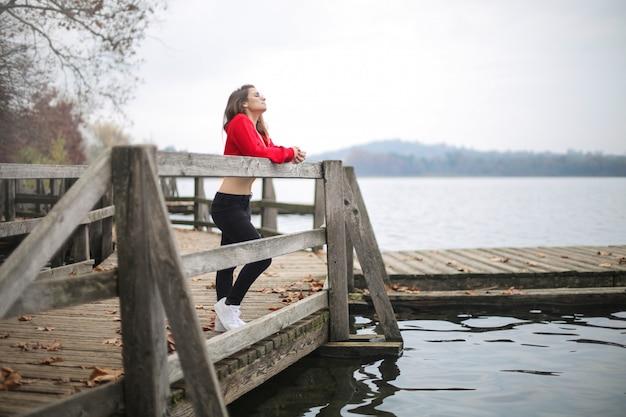 Ragazza che si distende, in piedi su un molo in un lago