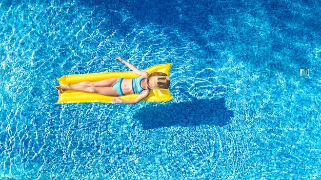 Ragazza che si distende in piscina, bambino nuota sul materasso gonfiabile e si diverte in acqua, località di villeggiatura tropicale, vista aerea del drone dall'alto