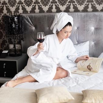 Ragazza che si rilassa e che mangia un bicchiere di vino