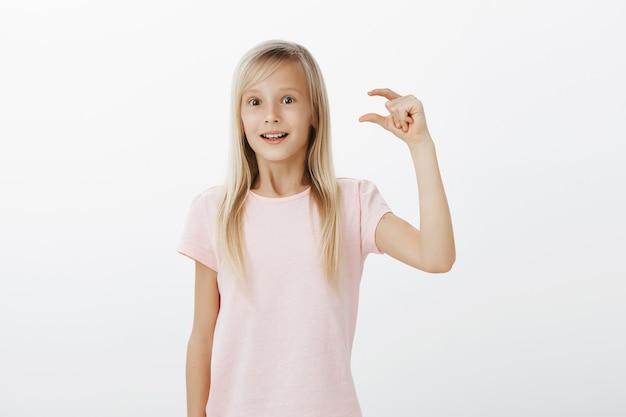 Ragazza che si sente ottimista ed eccitata, condividendo impressioni dopo aver visitato lo zoo. figlia bionda carina in maglietta rosa, alzando la mano e modellando cosa piccola o minuscola con espressione ammirata sul muro grigio
