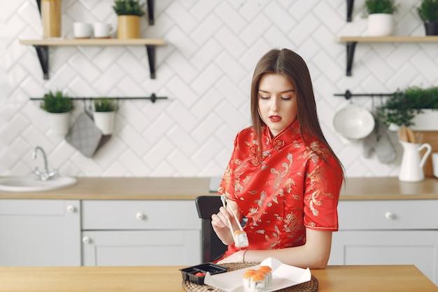 Ragazza che si siede a casa al tavolo con un sushi